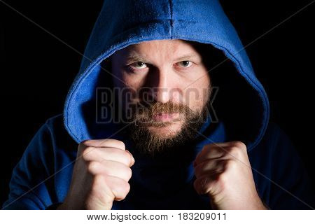 Portrait of a fighter in a hood on black background