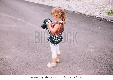 Little Girl With Big Camera In Hands Outdoors.