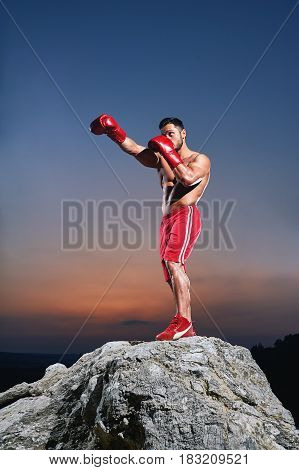 Focused young male boxer training outdoors wearing boxing gloves working out on sunset punching fighting muscles power strength confidence defense martial sports sportive body sexy handsome guy.