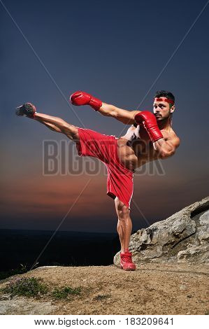 Vertical shot of a muscular strong male fighter practicing kickboxing training outdoors wearing boxing gloves sunset on the background sports motivation determination achievement strength combat