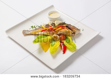 Grilled Whole Fish Decorated With Leaves Of Lettuce And Cherry Tomato, Served With Garlic Sauce. Fri