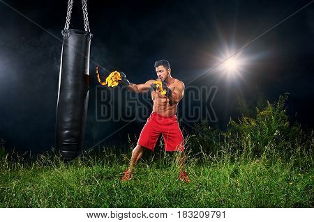 Full length shot of a muscular fit and toned young man boxing outdoors with burning boxing gloves training on a punching bag at night copyspace sports sportsman athlete athletics physique fitness.