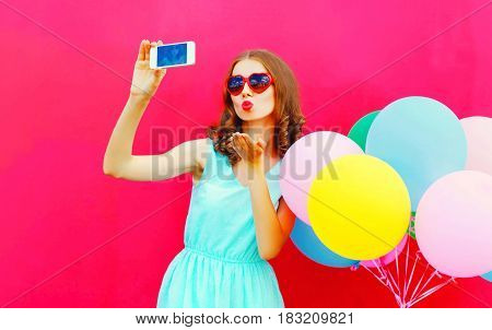 Fashion Pretty Woman Taking A Picture On A Smartphone Sends An Air Kiss Over An Air Colorful Balloon
