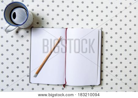 Sharp pencil is on white sheet of notebook. Mug with dark delicious coffee at table. Top view