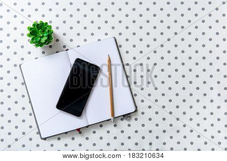 Pencil and smartphone are on open book. Diary is near little green herb. Top view. Copy space