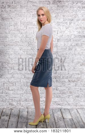 Blinde posing full-length in skirt and yellow chooses on brick gray background