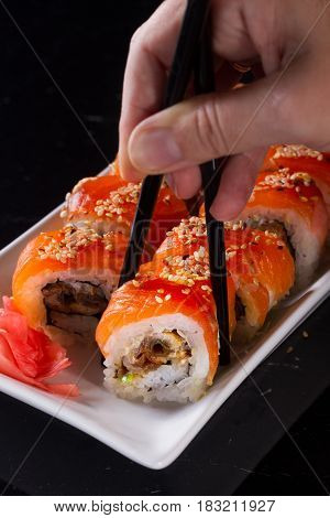 Japanese sushi rolls dish with hand holding one pice in chopsticks on black background