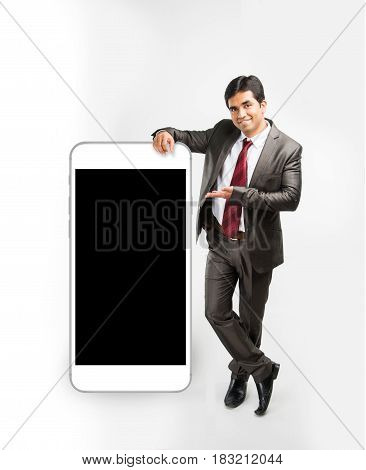 concept photo of an indian or asian businessman resting hand over big smartphone and in presenting pose, isolated over white background