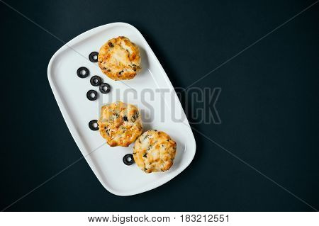 Cupcakes with spinach, cheese and vegetables on a black background. Healthy breakfast concept. Pieces of sliced olives.