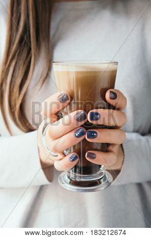 Close-up of beautiful female hands holding a large glass cup of coffee cappuccino. Woman wearing a warm winter knitted white sweater