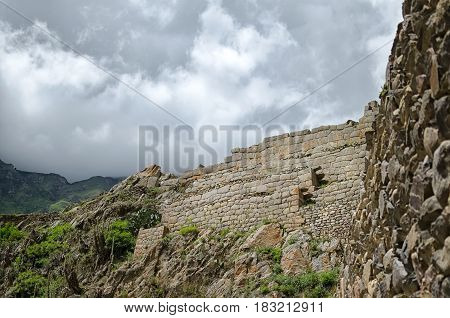 Ancient Inca wall lost in mountains under tragic sky