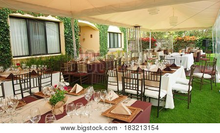 Tables decorated and arranged for a celebration in the garden of a house in the morning