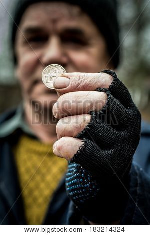 Metal coin, men are in the hand. on the hand wearing a glove with cut off fingers.