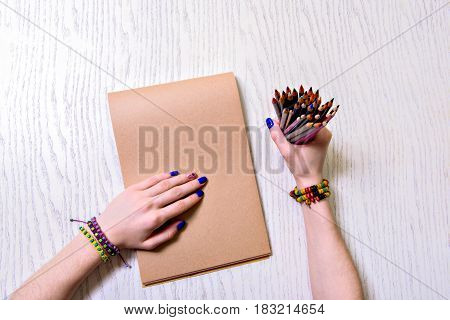Girl is clenching various colored pencils. She putting arm on drawing block. Top view