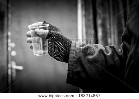 In the man's hand squeezed the plastic Cup. In a plastic Cup are different coins.