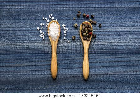 salt crystals and colour pepper on wooden spoons on wooden background