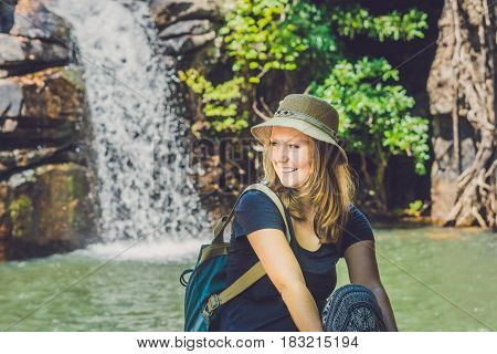 Young Woman Sits On A Waterfall Background