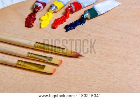 Different brushes are near open tubes of colorful paint at wooden pallet. Focus on tassel