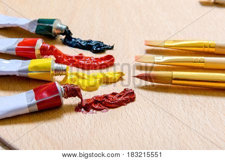 Open tubes, full of bright paint are afore handy brushes at wooden desk. Focus on equipment. Close-up