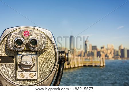 Close up of tower viewer binoculars with blurred New York City skyline in the background on Liberty Island. New York City Harbor and Lower Manhattan skyline on a bright sunny day shallow DoF.