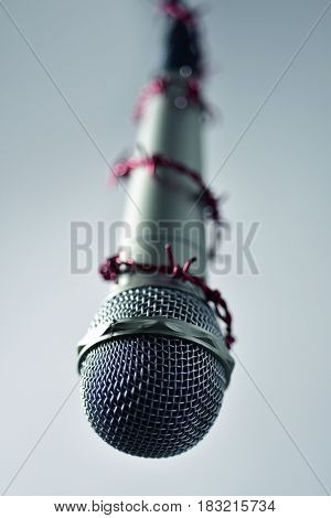 closeup of a microphone encircled by a red barbed wire, depicting the idea of the repression of the mass media or the lack of the freedom of speech