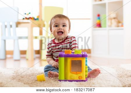 Baby boy playing with colorful toys at home. Happy seven months old infant child playing and discovery.