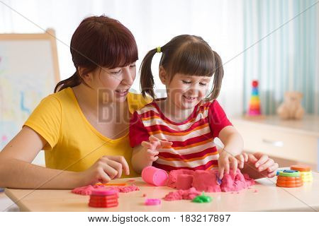 A cute little little girl and her mother playing with kinetic sand at home