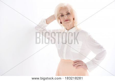 I am still young. Confident old lady is standing near wall and looking at camera with smile. Isolated