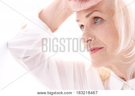Old lady with wisdom in sight is glancing up. She putting hand on her forehead. Isolated