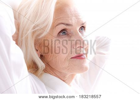 Thoughtful old lady is putting hands behind head and glancing up with light smile. Isolated