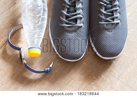 Gray sport shoes with chronometer and bottle of waterr. Pair of sneakers on wooden background