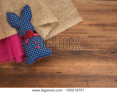 Vintage, rustic background with a toy rabbit on background of burlap and old wooden table. Top view.