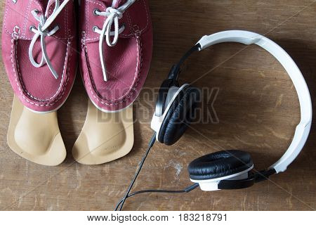 Pink sport shoes with orthopedic insoles and headphones. Pair of sneakers on wooden background