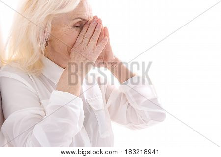 Mature lady is standing and touching to her face while covering smile. Isolated. Copy space