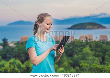 Young Woman Enjoys A Tablet On The Background Of The Sea