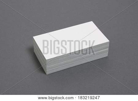 Blank business cards stacked up on a grey background