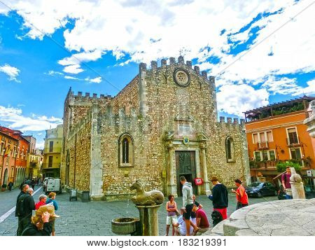 Taormina, Sicily, Italy - May 05, 2014: The people near Duomo Catherdal in Taormina city in Sicily. Cathedral of Taormina is a medieval church dedicated to St Nicholas of Bari or San Nicola di Bari