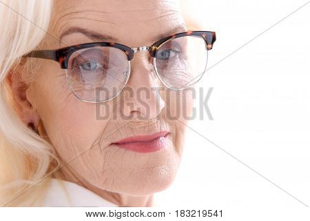 Interested mature lady in glasses is looking at camera with confidence. Isolated. Portrait. Copy space