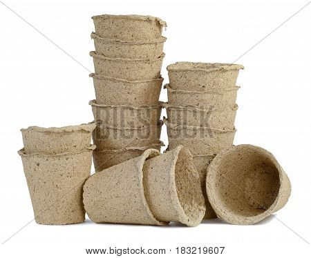 a bunch of pitchers cups of peat for seedlings of plants inserted into one another isolated on white background