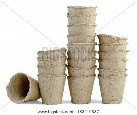 a lot of cups of peat for seedlings of plants inserted into one another and are installed in a row isolated on white background