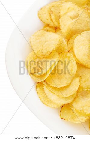 Crispy potato chips in the plate on white background close-up