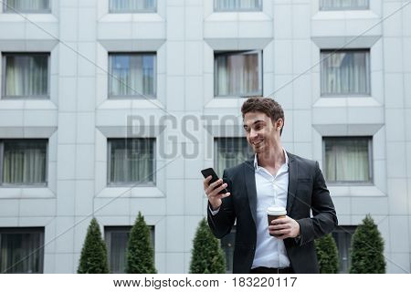 Cheerful businessman using smartphone in business center
