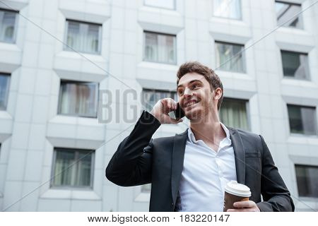 Young cheerful businessman talking on phone in business center