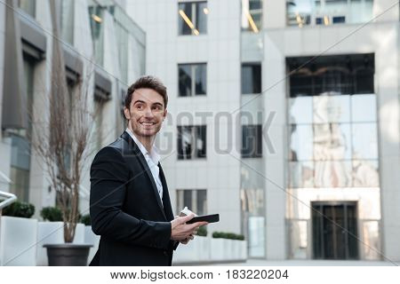 Smiling man looking away while going upstairs with coffee
