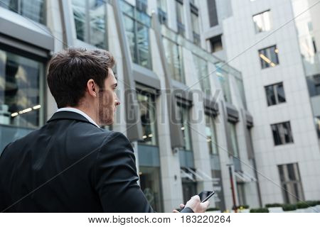 Back view of busy businessman with smartphone in large modern building