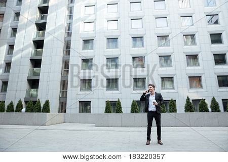 Shot of businessman talking on phone against large building