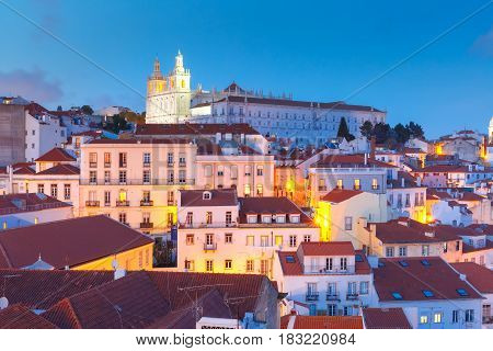 Scenic view of Alfama, the oldest district of the Old Town, with Monastery of Sao Vicente de Fora during evening blue hour, Lisbon, Portugal