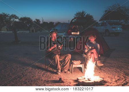 Adult Couple Relaxing In Camping Site By Night. Adventure In National Park, South Africa. Burning Ca