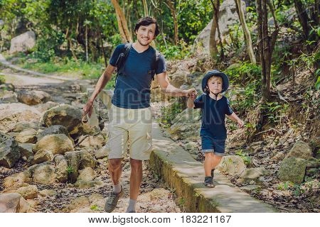Father And Son Are Walking Along The Forest Road