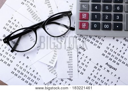 Calculator with glasses and calendar, closeup. Tax concept
